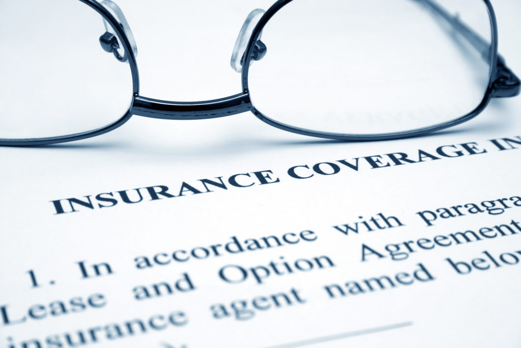 Close up of glasses on Insurance coverage form